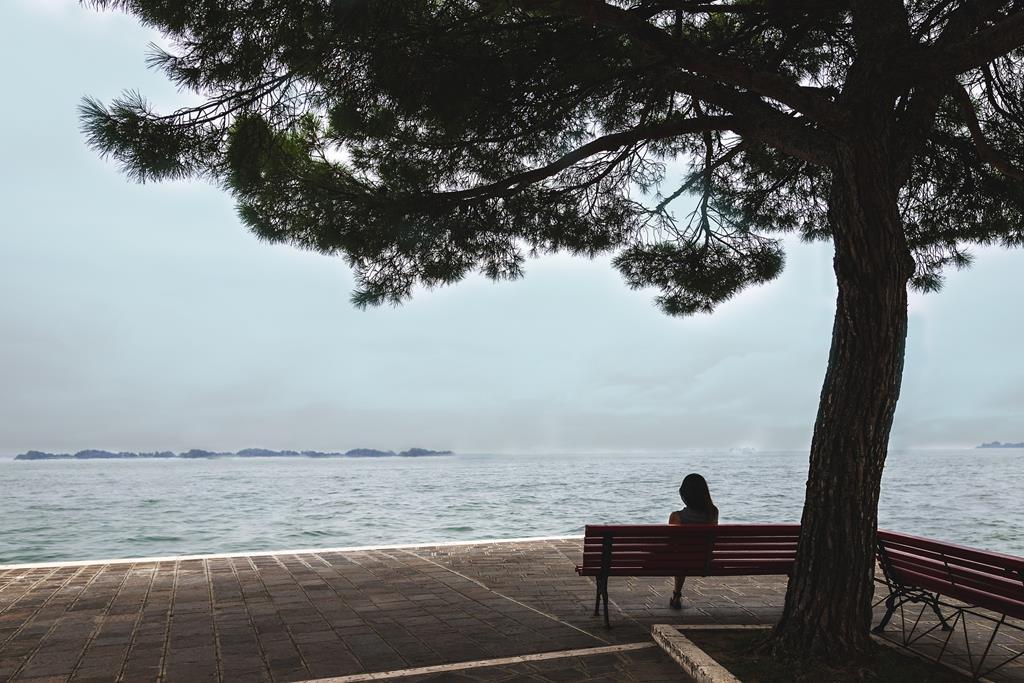 femme_assise_sur_un_banc_devant_la_mer